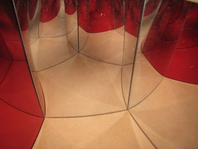 Using one red mirror shows how the extra hyperbolic space is folded away to fit in Euclidean space.